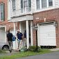 Law enforcement officers work outside the home of Nicholas Young on Aug. 3 in Fairfax, Virginia. Young, who worked as a Metro police officer, has been charged with helping the Islamic State but has not faced trial. (Associated Press)