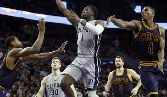 Detroit Pistons guard Reggie Jackson (1) goes to the basket while defended by Cleveland Cavaliers center Tristan Thompson, left, and guard Iman Shumpert (4) during the first half of an NBA basketball game, Monday, Dec. 26, 2016, in Auburn Hills, Mich. (AP Photo/Duane Burleson)