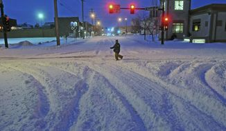 Madori Griffin, who says her car was snowed in, makes her way through an intersection while walking to work in the intensive care unit of Sanford Hospital early Monday, Dec. 26, 2016, in Bismarck, N.D. The combination of freezing rain, snow and high winds that forced the shutdown Sunday of vast stretches of highways in the Dakotas continued into Monday morning, and authorities issued no-travel warnings for much of North Dakota. (Tom Stromme/The Bismarck Tribune via AP)