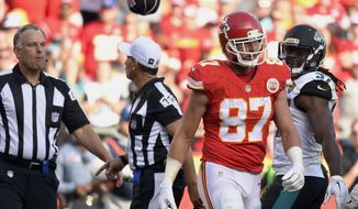 FILE - In this Nov. 6, 2016, file photo, field Judge Mike Weatherford, left, throws his cap toward Kansas City Chiefs tight end Travis Kelce (87) after Kelce, who was ejected for unsportsmanlike conduct, threw a towel in his direction during the second half of an NFL football game against the Jacksonville Jaguars in Kansas City, Mo. This was the year of the penalty in the NFL. Not so much because more flags were thrown in 2016 than last season, but because the questioning of the competence of the officials began, literally, on opening day and continued, in some form, virtually every week, without a stop. (AP Photo/Ed Zurga, File)