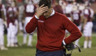 FILE - In this Nov. 28, 2015, file photo, Connecticut head coach Bob Diaco looks down as he rubs his head during the second half of an NCAA college football game against the Temple in Philadelphia. UConn athletic director David Benedict announced Monday, Dec. 26, 2016, that head football coach Bob Diaco has been relieved of his coaching duties, effective Jan. 2.  (AP Photo/Chris Szagola, File)