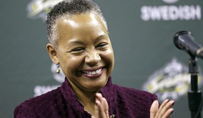 FILE- In this April 21, 2016, file photo, WNBA president Lisa Borders applauds at a Seattle Storm news conference in Seattle. The WNBA is offering a security app to its players to help them stay safer while they are overseas this offseason. (AP Photo/Elaine Thompson, File)
