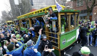 FILE - In this Dec. 13, 2016 file photo, Seattle Sounders forward Nicolas Lodeiro, center, holds the MLS Cup trophy for fans to touch as he rides a trolly with teammates during a championship celebration march in Seattle. The Sounders championship was among the top news stories in Washington state in 2016. (AP Photo/Ted S. Warren, File)
