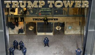 Police stand outside the Fifth Avenue, public, entrance to Trump Tower, Tuesday, Nov. 15, 2016, in New York. For nearly the entire week since he became president-elect, Donald Trump has been holed up in Trump Tower, his gilded New York skyscraper. A steady stream of visitors has come to him, flooding through metal detectors and getting whisked up to Trump's offices and penthouse residence. (AP Photo/Kathy Willens)