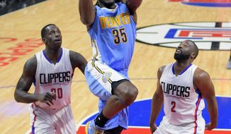 Denver Nuggets forward Kenneth Faried, center, shoots as Los Angeles Clippers forward Brandon Bass, left, and guard Raymond Felton defend during the first half of an NBA basketball game, Monday, Dec. 26, 2016, in Los Angeles. (AP Photo/Mark J. Terrill)