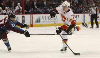 Calgary Flames center Sam Bennett, right, takes a shot as Colorado Avalanche left wing Andreas Martinsen, of Norway, defends in the second period of an NHL hockey game, Tuesday, Dec. 27, 2016, in Denver. (AP Photo/David Zalubowski)