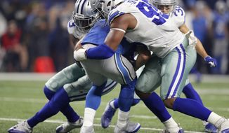 Dallas Cowboys' Benson Mayowa, left, and David Irving (95) combine to sack Detroit Lions' Matthew Stafford, center, in the first half of an NFL football game, Monday, Dec. 26, 2016, in Arlington, Texas. (AP Photo/Brandon Wade)