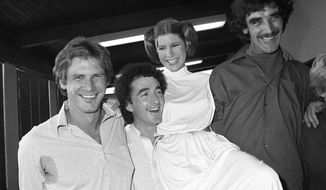 From left, actors Harrison Ford, Anthony Daniels, Carrie Fisher and Peter Mayhew take a break from filming a television special in Los Angeles to be telecast during the holidays, Oct. 5, 1978. On Tuesday, Dec. 27, 2016, a publicist says Fisher has died at the age of 60. (AP Photo/George Brich, File) ** FILE **