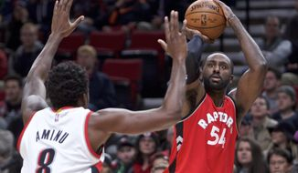 Toronto Raptors forward Patrick Patterson, right, shoots over Portland Trail Blazers forward Al-Farouq Aminu during the first half of an NBA basketball game in Portland, Ore., Monday, Dec. 26, 2016. (AP Photo/Craig Mitchelldyer)