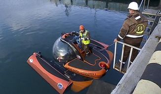 In this Tuesday, Dec. 27, 2016 frame grab made available by Russian Rossiya One TV Channel Emergency Ministry employees prepare a submersible to make it ready to join the search for bodies and fragments of the crashed plane, on a pier just outside Sochi, Russia. (Rossiya One TV Channel photo via AP)  MANDATORY CREDIT