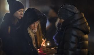 Women try to light a candle to place with flowers in front of the Alexandrov Ensemble building in Moscow, Russia, Monday, Dec. 26, 2016, the day after a plane carrying 64 members of the Alexandrov Ensemble crashed into the Black Sea minutes after taking off from the resort city of Sochi. (AP Photo/Alexander Zemlianichenko)