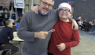 In this Dec. 20, 2016 photo, Thunder Mountain High School Principal Dan Larson, left, poses for photos with Mitchell Henderson, one of the students from Juneau-Douglas High School that spent a lunch hour handing out candy canes to students at Thunder Mountain High School in Juneau, Alaska. Students passed out candy canes as part of a kindness campaign spearheaded by the Juneau Police Department that officially kicks off with the New Year. (AP Photo/Becky Bohrer)