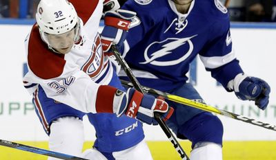 Montreal Canadiens center Brian Flynn (32) loses the puck as he collides with Tampa Bay Lightning left wing Jonathan Drouin (27) during the first period of an NHL hockey game Wednesday, Dec. 28, 2016, in Tampa, Fla. (AP Photo/Chris O'Meara)