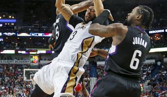 New Orleans Pelicans forward Anthony Davis (23) is stopped as he goes to the basket between Los Angeles Clippers' DeAndre Jordan (6) and Marreese Speights (5) during the first half of an NBA basketball game in New Orleans, Wednesday, Dec. 28, 2016. (AP Photo/Gerald Herbert)