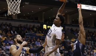 Marquette's Jajuan Johnson dunks past Georgetown's Bradley Hayes (42) and Rodney Pryor during the first half of an NCAA college basketball game Wednesday, Dec. 28, 2016, in Milwaukee. (AP Photo/Morry Gash)