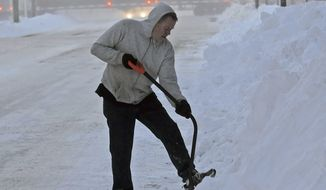 Kenny Eide works at digging hard pack snow to open an access walkway for residents living at the former Prince Hotel in downtown Bismarck, ND., as a train passes by in the background on Tuesday morning, Dec. 27, 2016. Many streets in Bismarck and Mandan remain covered by snow as both cities begin the process of digging out from the two-day Christmas Day blizzard of 2016 (Tom Stromme/The Bismarck Tribune via AP)