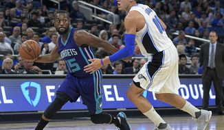 Charlotte Hornets guard Kemba Walker (15) drives past Orlando Magic forward Aaron Gordon (00) during the first half of an NBA basketball game in Orlando, Fla., Wednesday, Dec. 28, 2016. (AP Photo/Phelan M. Ebenhack)