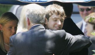 In this June 29, 2006, file photo, John Ramsey hugs his son, Burke, facing camera, at the graves of his wife, Patsy, and daughter JonBenet, during services for his wife at the St. James Episcopal Cemetery in Marietta, Ga. Burke Ramsey is suing CBS and others for $750 million over a series that aired in September 2016 that Ramsey alleges concluded he killed his sister. (AP Photo/Ric Feld, File)