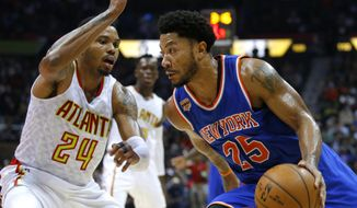 New York Knicks guard Derrick Rose (25) drives to the basket as Atlanta Hawks forward Kent Bazemore (24) defends in the second half of an NBA basketball game on Wednesday, Dec. 28, 2016, in Atlanta. Atlanta won the game 102-98 in overtime. (AP Photo/Todd Kirkland)