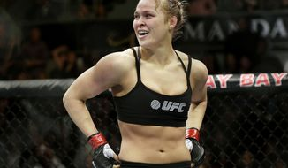 FILE - In this Feb. 22, 2014, file photo, Ronda Rousey looks around after defeating Sara McMann in a UFC 170 mixed martial arts women's bantamweight title bout in Las Vegas. Rousey is returning to the UFC on Friday, Dec. 30, 2016, after a 13-month absence, taking on Amanda Nunes for the bantamweight title. The formerly dominant champion has declined to promote her comeback fight. (AP Photo/Isaac Brekken, File)