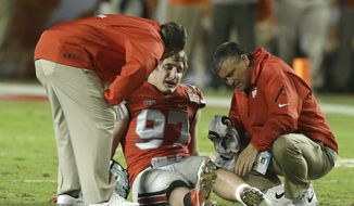 FILE - This Jan. 3, 2014 file photo shows Ohio State defensive lineman Joey Bosa being attended to after a play during the first half of the Orange Bowl NCAA college football game between Clemson and Ohio State in Miami Gardens, Fla. Ohio State's defense had been laid to waste by Clemson in the 2014 Orange Bowl, the last in a series of lousy performances by the Buckeyes that caused a promising season to end with a thud. When No. 2 Ohio State (11-1, No. 3 CFP) faces No. 3 Clemson (12-1, CFP No. 2) in the Fiesta Bowl semifinal on Saturday at University of Phoenix Stadium, the Tigers will be dealing with a very different animal. (AP Photo/Wilfredo Lee, file)