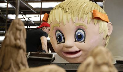 Volunteer Ivo Angelov holds a small brush in his mouth while decorating a float ahead of next week's 128th Rose Parade Wednesday, Dec. 28, 2016, in Irwindale, Calif. (AP Photo/Jae C. Hong)