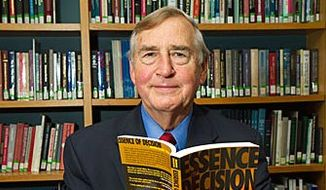 Graham T. Allison Jr., Douglas Dillon Professor of Government in the John F. Kennedy School of Government and Director of Belfer Center for Science and International Affairs at the JFK School of Government, poses with his book about the Cuban missile crisis of 1962. Jon Chase/Harvard Staff Photographer