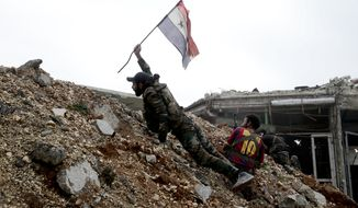 FILE - A Syrian army soldier places a Syrian national flag during a battle with rebel fighters at the Ramouseh front line, east of Aleppo, Syria, Monday, Dec. 5, 2016. (AP Photo/Hassan Ammar, File)