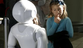 In this Thursday, Dec. 22, 2016, photo, Emerson Hill, 6, plays with Pepper the robot at Westfield Mall in San Francisco. While merrily chirping, dancing and posing for selfies, Pepper looks like another expensive toy in the San Francisco mall where it will be entertaining shoppers through mid-February. But it would be a mistake to dismiss Pepper as mere child's play, even though kids flock around the 4-foot-tall humanoid as it speaks in a cherubic voice that could belong to either a boy or girl. (AP Photo/Jeff Chiu)