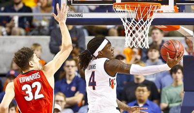 Auburn guard T.J. Dunans scores against Georgia forward Mike Edwards during the first half of an NCAA college basketball game, Thursday, Dec. 29, 2016, in Auburn, Ala. (AP Photo/Brynn Anderson)