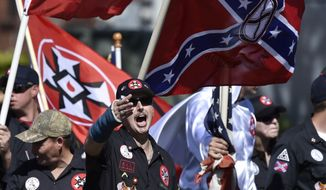 """In this Saturday, April 23, 2016 file photo, Loyal White Knights Grand Dragon Will Quigg of Anaheim, Calif., center, shouts to protestors during a """"White Pride"""" rally, in Rome, Ga. (AP Photo/Mike Stewart)"""