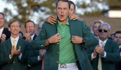FILE- In this April 10, 2016, file photo, defending champion Jordan Spieth, rear, helps 2016 Masters champion Danny Willett, of England, put on his green jacket following after Willett won the Masters golf tournament in Augusta, Ga. (AP Photo/Jae C. Hong, File)