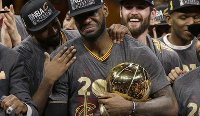 FILE - In this June 19, 2016, file photo, Cleveland Cavaliers forward LeBron James, center, celebrates with teammates, including Kevin Love, third from left, after they won Game 7 of basketball's NBA Finals against the Golden State Warriors in Oakland, Calif. (AP Photo/Marcio Jose Sanchez, File)