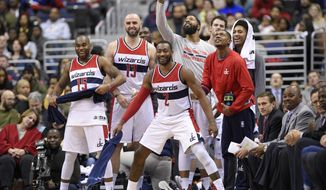 Washington Wizards' John Wall (2), Marcus Thornton (15), Marcin Gortat (13), Markieff Morris, pointing, Bradley Beal, in red, and forward Kelly Oubre Jr. right, react during the second half of the team's NBA basketball game against the Brooklyn Nets, Friday, Dec. 30, 2016, in Washington. The Wizards won 118-95. (AP Photo/Nick Wass)