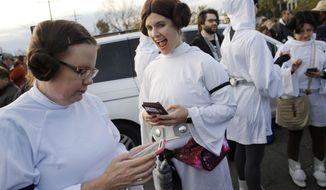 """Members of the Krewe of Chewbacchus, a Mardi Gras Krewe, dressed as Princess Leia, use their smart phones at the start of a parade in honor of actress Carrie Fisher, who played Leia in the """"Star Wars"""" movie series, in New Orleans, Friday, Dec. 30, 2016. Fisher died on Dec. 27, 2016, at the age of 60. (AP Photo/Gerald Herbert)"""