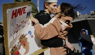 """In costume and carrying a sign reading """"Have u seen my significant otter?"""" Melanie Till welcomes her husband, P.O. 3rd Class David Till, home after the USS Dwight D. Eisenhower returned to Naval Station Norfolk, in Norfolk, Va., on Friday, Dec, 30, 2016, from a seven-month deployment to the Middle East and the Mediterranean Sea. (Stephen M. Katz/The Virginian-Pilot via AP)"""