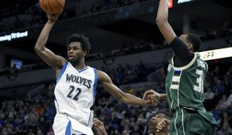 Minnesota Timberwolves forward Andrew Wiggins (22) passes away from Milwaukee Bucks forward Giannis Antetokounmpo, of Greece, and center John Henson (31) during the second quarter of an NBA basketball game on Friday, Dec. 30, 2016, in Minneapolis. (AP Photo/Hannah Foslien)
