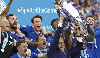 FILE - In this May 7, 2016, file photo, Leicester manager Claudio Ranieri and Leicester's Wes Morgan lift the trophy as Leicester City celebrate becoming the English Premier League soccer champions at King Power stadium in Leicester, England. (AP Photo/Matt Dunham, File)