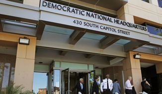 In this June 14, 2016 file photo, people stand outside the Democratic National Committee (DNC) headquarters in Washington. (AP Photo/Paul Holston, File)