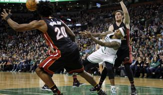 Boston Celtics guard Isaiah Thomas (4)  passes after driving against Miami Heat forwards Luke Babbitt (5) and Justise Winslow (20) in the first quarter of an NBA basketball game, Friday, Dec. 30, 2016, in Boston. (AP Photo/Elise Amendola)