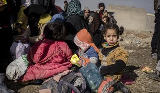 Iraqis displaced from Mosul wait for transportation to IDP camps, near Bartella, Iraq on Thursday, Dec. 29, 2016. Breaking a two-week lull in fighting, Iraqi troops backed by the U.S.-led coalition's airstrikes and artillery pushed deeper into eastern Mosul on Thursday in a multi-pronged assault against Islamic State militants in the city. (AP Photo/Cengiz Yar)
