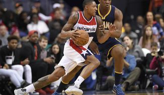 Washington Wizards guard Bradley Beal dribbles against Indiana Pacers center Kevin Seraphin, back, during the first half of an NBA basketball game, Wednesday, Dec. 28, 2016, in Washington. (AP Photo/Nick Wass)