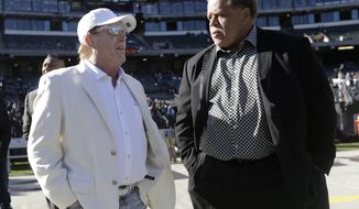 FILE - In this Saturday, Dec. 24, 2016 file photo, Oakland Raiders owner Mark Davis, left, talks with general manager Reggie McKenzie before an NFL football game against the Indianapolis Colts in Oakland, Calif. When the Raiders lost the first 10 games in McKenzie's third season back in 2014, and fired his hand-picked coach and fell to 11-37 under his leadership, few would have questioned Davis had he decided to make a change. Instead, Davis stuck with McKenzie and is receiving the dividends for his patience this season. (AP Photo/Marcio Jose Sanchez, File)
