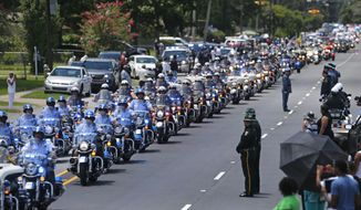 FILE - In this July 25, 2016 file photo, the funeral procession for slain Baton Rouge police Corporal Montrell Jackson leaves the Living Faith Christian Center in Baton Rouge, La. Jackson, slain by a gunman who authorities said targeted law enforcement. The number of police killed in the line of duty rose sharply in 2016, driven by shootings of police around the country, most notably ambushes in Dallas and Baton Rouge, Louisiana.From Jan. 1 through Wednesday, 135 officers lost their lives. Some died in traffic accidents, but nearly half were shot to death.  (AP Photo/Gerald Herbert, File)