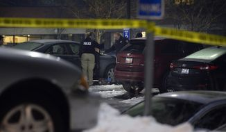 Police investigate a fatal shooting which took place next to this silver/blue sedan in a parking lot near the University of Utah in Salt Lake City, Thursday, Dec. 29, 2016. University of Utah police say a man and woman have been fatally shot in a parking lot and authorities suspect it's a case of murder-suicide. Police spokesman Garth Smith says the woman was found dead at the scene and the man died later at the hospital.  (Scott Sommerdorf/The Salt Lake Tribune via AP)