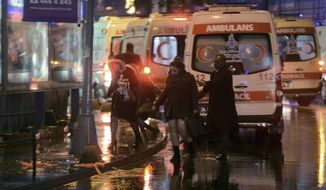 People leave as medics and security officials work at the scene after an attack at a popular nightclub in Istanbul, early Sunday, Jan. 1, 2017. Turkey's state-run news agency says an armed assailant has opened fire at a nightclub in Istanbul during New Year's celebrations, wounding several people.(IHA via AP)