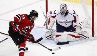 New Jersey Devils center Adam Henrique (14) skates in on Washington Capitals goalie Philipp Grubauer (31), of Germany, during the third period of an NHL hockey game, Saturday, Dec. 31, 2016, in Newark, N.J. (AP Photo/Julio Cortez)
