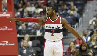 Washington Wizards guard John Wall (2) points during the first half of an NBA basketball game against the Brooklyn Nets, Friday, Dec. 30, 2016, in Washington. (AP Photo/Nick Wass)
