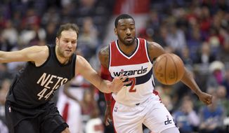 Washington Wizards guard John Wall (2) chases the loose ball against Brooklyn Nets guard Bojan Bogdanovic (44), of Croatia, during the first half of an NBA basketball game, Friday, Dec. 30, 2016, in Washington. (AP Photo/Nick Wass)