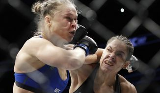 Amanda Nunes, right, connects with Ronda Rousey in the first round of their women's bantamweight championship mixed martial arts bout at UFC 207, Friday, Dec. 30, 2016, in Las Vegas. Nunes won the fight after it was stopped in the first round. (AP Photo/John Locher)